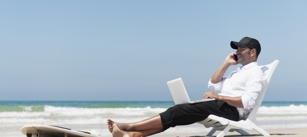 A Businessman Sits On A Beach Chair On The Beach Working On A Laptop Computer And Talking On The Phone With His Surfboard Sitting At His Feet; Tarifa Cadiz Andalusia Spain --- Image by © Ben Welsh/Design Pics/Corbis